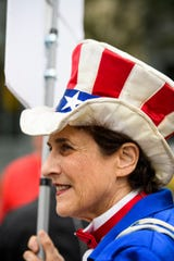 Carol Dunitz dressed as Uncle Sam protests outside of the South Carolina Democratic debate in Charleston Tuesday, Feb. 25, 2020.
