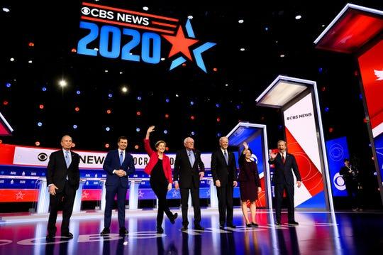 Democratic presidential candidates Michael Bloomberg, Pete Buttigieg, Elizabeth Warren, Bernie Sanders, Joe Biden, Amy Klobuchar and Tom Steyer walk onto the stage during the Feb. 25 South Carolina Democratic debate in Charleston.