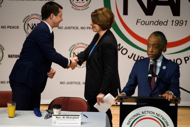 Democratic presidential candidates Pete Buttigieg and Amy Klobuchar shake hands during a National Action Network breakfast at Mt. Moriah Missionary Baptist Church in Charleston Wednesday, Feb. 26, 2020.