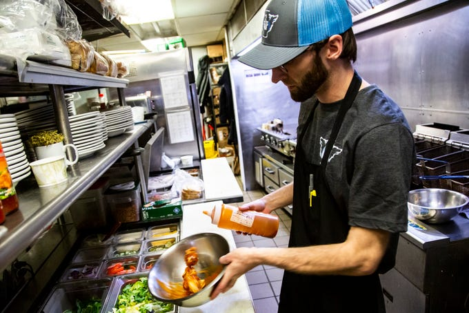 Dan Pray, a line cook at 2 Dogs Pub, tosses chicken wings in buffalo sauce, Wednesday, Feb. 26, 2020, at 2 Dogs Pub in Iowa City, Iowa.