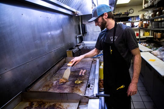 Dan Pray, a line cook at 2 Dogs Pub, prepares the Alabama burger, Wednesday, Feb. 26, 2020, at 2 Dogs Pub in Iowa City, Iowa. The burger is an angus beef patty with jalapeños, bacon, caramelized onions, cheddar cheese, and a chipotle citrus barbecue sauce