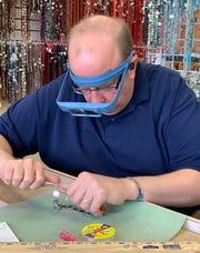 Jim Bankston repairs a bracelet for a customer at Village Beads in Ridgeland.