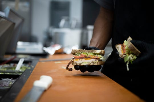 Dewayne Brown shows off one of the craft sandwiches from Hub City Deli in Jackson, Tenn., Thursday, Feb. 20, 2020.