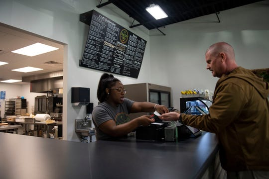 Employee Alexus Cooley gives change to a customer at Hub City Deli in Jackson, Tenn., Thursday, Feb. 20, 2020.