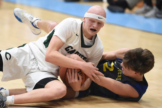 Carter's Ty Hurst (1) and Gatlinburg-Pittman's Briggs Jones (2) battle for the control of the ball in the District 3-AA basketball championship at Gibbs High School on Tuesday, February 25, 2020.