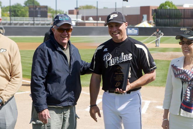 Former Purdue baseball coach Dave Alexander presents a plaque to Doug Schreiber, who passed Alexander as the program's all-time winningest coach. Alexander died Wednesday