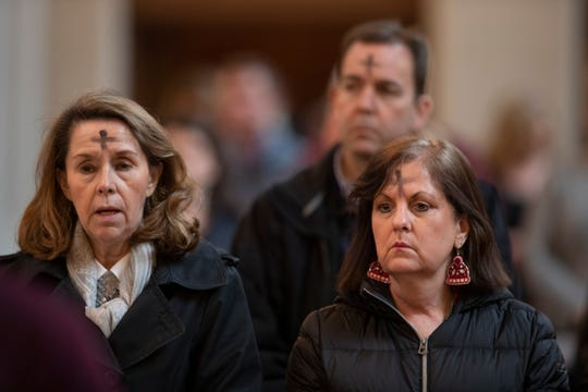 Worshipers are seen wearing the cross of ashes during a service at the Cathedral of the Assumption to mark the beginning of Lent. Feb. 26, 2020.