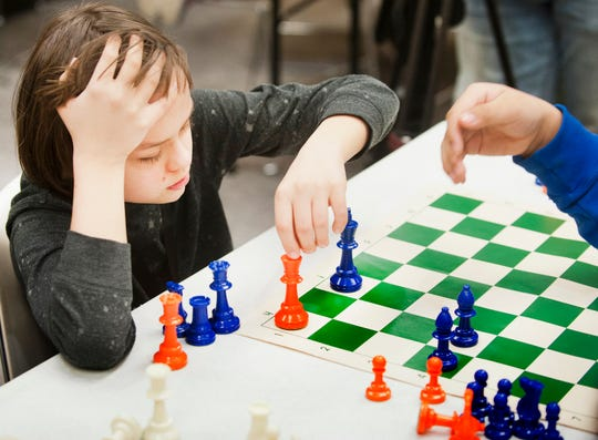 Rhodi McNamara, 11, left, makes a move in an end-game exercise during a West Louisville Chess Club practice.