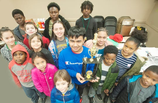 Members of the West Louisville Chess Club hold up a first place team trophy they won at a recent tournament.