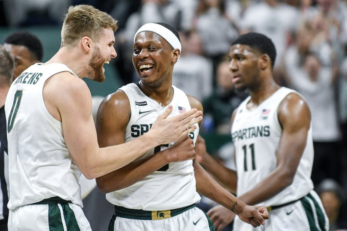 Michigan State's Kyle Ahrens, left, and Cassius Winston celebrate during a timeout during the second half on Tuesday, Feb. 25, 2020, at the  Breslin Center in East Lansing.