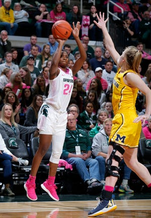 Michigan State's Nia Clouden, left, shoots against Michigan's Maddie Nolan during the second half of an NCAA college basketball game, Sunday, Feb. 23, 2020, in East Lansing, Mich. Michigan won 65-57. (AP Photo/Al Goldis)