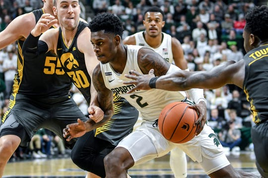 Michigan State's Rocket Watts, center, moves between Iowa's Joe Toussaint, right, and Connor McCaffery on his way to a layup during the first half on Tuesday, Feb. 25, 2020, at the  Breslin Center in East Lansing.