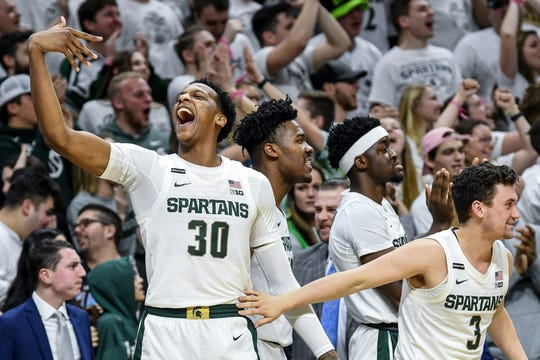 Michigan State's Marcus Bingham Jr., left, and the bench celebrates during the second half on Tuesday, Feb. 25, 2020, at the  Breslin Center in East Lansing.