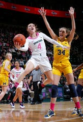 Michigan State's Taryn McCutcheon, left, puts up a driving layup-attempt against Michigan's Izabel Varejao (34) during the second half of an NCAA college basketball game, Sunday, Feb. 23, 2020, in East Lansing, Mich. (AP Photo/Al Goldis)