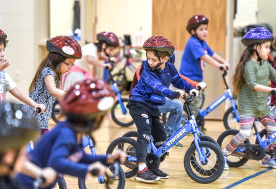 Kindergarten students play games as part of the lessons to learn to ride bikes through the All Kids Bike program.