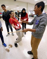 Dildar Mohamad Alam, a student at Milwaukee Public Schools' International Newcomer Center, learns how to use a Chinese yo-yo from Peter Kao during a Chinese New Year program at the Milwaukee Academy of Chinese Language. The center, which is housed in MACL, serves mostly refugee students with a program that marries subject matter content with English as a second language.