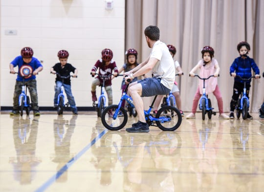 Through the All Kids Bike program, physical education teachers teach kindergarten classes how to ride bikes.