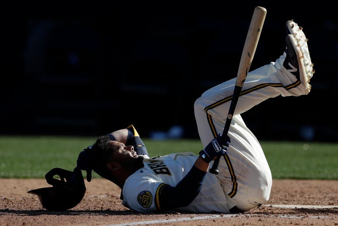 Andres Blanco of the Brewers lands on his back after being hit by a pitch during the ninth innings against the Mariners on Tuesday.
