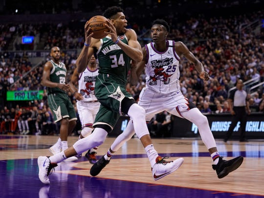 Bucks forward Giannis Antetokounmpo drives to the basket past Raptors forward Chris Boucher Tuesday night.