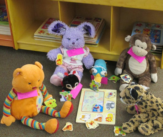 A group of stuffed animals work on a puzzle at a previous stuffed animal sleepover held at the Baxter County Library.