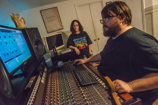 Chris Lantrip, right, and Andie Schultz in Headless Dinosaur Recording's control room, which is upstairs in their Montgomery home.