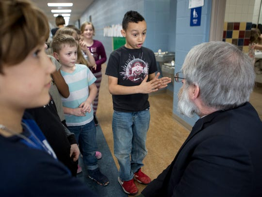 Paolo DeMaria, Ohio's Superintendent of Public Instruction talks with John Clem second grader Donald Faller about what he and his classmates like about the Sensory Walk in their hallway. DeMaria was visiting Newark school Tuesday to see how they implement different techniques to help kids with mental health.