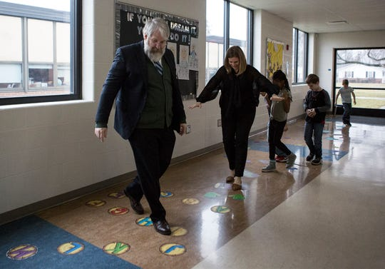 Paolo DeMaria, Ohio's Superintendent of Public Instruction and Ohio Board of Education member, Stephanie Dodd walk a hallway at John Clem know as the Sensory Walk. The interactive walk helps kids focus and calm themselves down. DeMaria was visiting Newark school Tuesday to see how they implement different techniques to help kids with mental health.