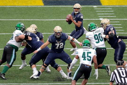 In this Oct. 26, 2019, file photo, Navy offensive guard David Forney, far right, blocks Tulane defensive end Davon Wright (90) as quarterback Malcolm Perry (10) looks to pass in the first half of an NCAA college football game in Annapolis.