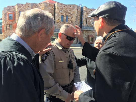 "Doña Ana County Sheriff's Office deputy Robbie Acosta gets ashes on his forehead by Rev. Wally LaLone and other members of St. Andrew's Episcopal Church on University Avenue, during the church's ""Ashes to Go"" service on Ash Wednesday. The church performed ash services along University Avenue near Espina Street for those who could not attend services at a church around town."