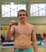 Las Cruces High School senior Asa Mynatt holds up his first-place medal in the 100 Freestyle at the State Championships in Albuquerque.
