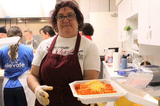 Volunteer Ramona Moseley serves a fresh batch of cheese enchilada's at St. Mary's annual cheese enchilada takeout fundraiser in Farmington on Feb. 26.