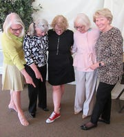 Admiring the ruby red sneakers of author Elizabeth Letts are Nancy Cunningham, Donna Martin, county librarian Barbara Howison and Carrie Brookshire.