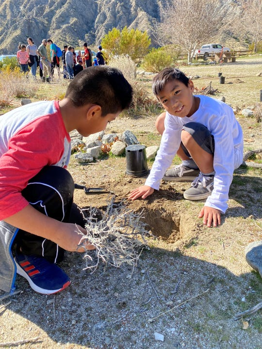 Two fourth graders measure the hole for planting a narrowleaf goldenbush.