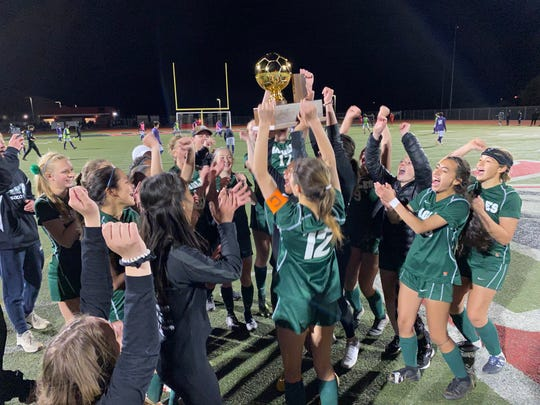 Flagstaff senior defender Maya Shearon hoists the 4A girls soccer state championship trophy into the air Tuesday night at Gilbert Williams Field High School after stunning Catalina Foothills in penalty kicks.