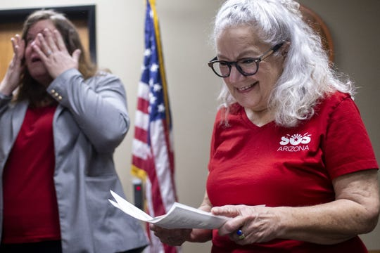 Cathy Sigmon looks at stamped paperwork for a new ESA initiative to limit school vouchers on Feb. 26, 2020, at the Arizona Secretary of State's Office at the Arizona state Capitol in Phoenix.