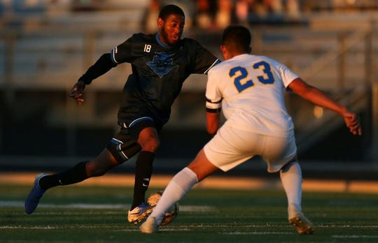 Sunnyside Blue Devils Demille Flores (18) pushes the ball up the field as Carl Hayden Falcons defender Christian Mendivil (C) (23) comes in to try and steal during the 5A boys state soccer championship game hosted at Mountain View High School in Marana, on Feb. 25, 2020.