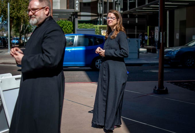 """Arizona Episcopal Diocese employee Jana Sundin and Trinity Episcopal lay Eucharistic Minister Rocko Cook wait at their """"Ashes to go"""" station in downtown Phoenix for Ash Wednesday, a Christian holiday of prayer and fasting that opens the holiday Lent, on Feb. 25, 2020."""