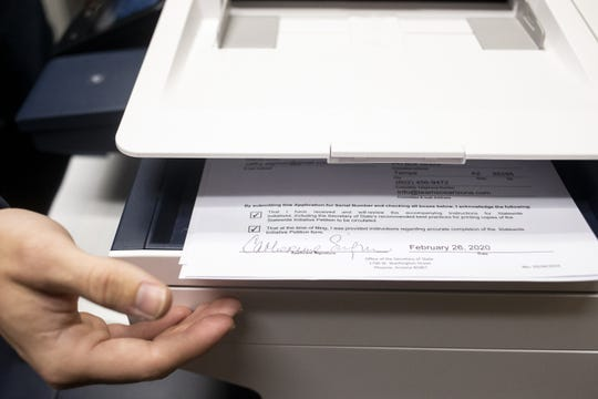 Chris Rhode, elections analyst at the Arizona Secretary of State's Office, prints copies of paperwork for a new ESA initiative to limit school vouchers on Feb. 26, 2020, at the Arizona state Capitol in Phoenix.