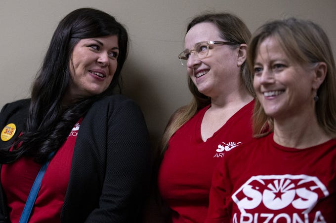 Beth Lewis (left) and Kate Tice smile at each other while Sharon Kirsch watches as Chris Rhode, elections analyst for the Arizona Secretary of State, checks paperwork for a new ESA initiative to limit school vouchers on Feb. 26, 2020, at the Arizona state Capitol in Phoenix.