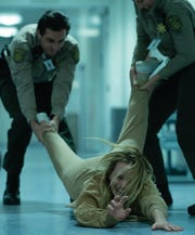"""Cecilia Kass (Elisabeth Moss, center) and police officers in """"The Invisible Man,"""" written and directed by Leigh Whannell."""