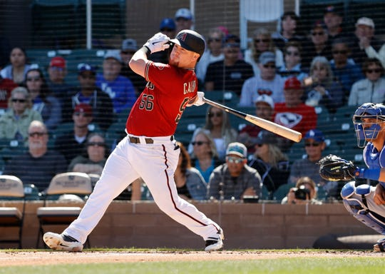 Arizona Diamondbacks Kole Calhoun hits an RBI-single to left field scoring Ketel Marte against the Los Angeles Dodgers in the first inning during a Cactus League game on Feb. 25, 2020 at Salt River Fields at Talking Stick in Scottsdale, Ariz.
