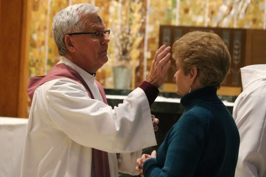 The Rev. John Missler of Immaculate Conception Church marks a cross on the forehead of Margaret Phillips, Port Clinton city councilwoman, during the service on Ash Wednesday services Feb. 17.