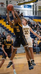 Port Huron Northern's Ryan McNeill jumps for a rebound with Fraser's Garrett Moore Tuesday, Feb. 25 during their basketball game at Port Huron Northern.