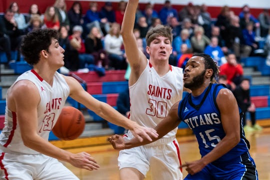 St. Clair's Ryan Zimmer (13) and Colin Zimmer (30) defend against Warren Woods-Tower's Dwayne Ware during Round 2 of the MAC Blue/Gold Tournament Tuesday, Feb. 25, 2020, at St. Clair High School.