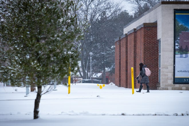 A student walks through snow on SC4's downtown campus Wednesday, Feb. 26, 2020, in downtown Port Huron.