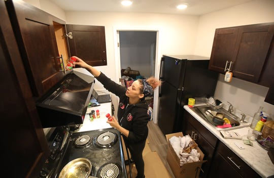 Barbara Rivera, Rochester, unpacks her kitchen as she moves back into the Apartments at Thurston Village at 447 Thurston Road in Rochester Wednesday, Feb. 26, 2020.