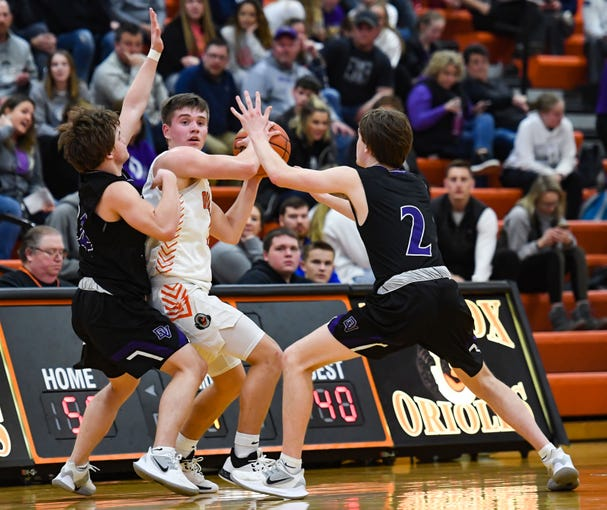 Josh Arlt of Lennox is guarded by both Drew Addison and Chayce Montagne of Dakota Valley during their game on Tuesday night, Feb. 25, at Lennox High School.