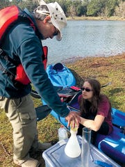 Ray Diaz and Elizabeth Wixted collect water samples from Lake Becky.