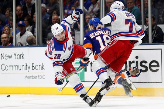 New York Rangers left wing Chris Kreider (20) and center Filip Chytil (72) collide as New York Islanders left wing Anthony Beauvillier (18) skates between them during the first period of an NHL hockey game, Tuesday, Feb. 25, 2020, in Uniondale, N.Y. (AP Photo/Kathy Willens)
