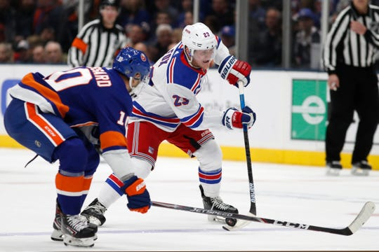 New York Islanders center Derick Brassard (10) defends as New York Rangers defenseman Adam Fox (23) prepares to take a shot on goal during the first period of an NHL hockey game, Tuesday, Feb. 25, 2020, in Uniondale, N.Y. (AP Photo/Kathy Willens)